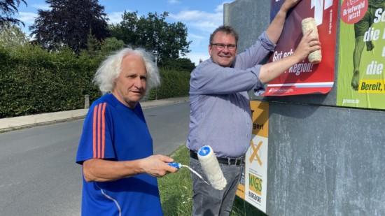 Die Kandidaten Helmut Wolynski und Matthias Paul kleben diverse Regions-Themenplakate auf Metalltafeln