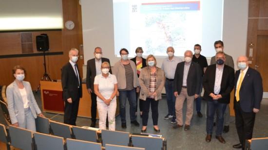 13 Personen stehen mit Mund-Nasen-Schutz in einem Hörsaal vor einer Leinwand