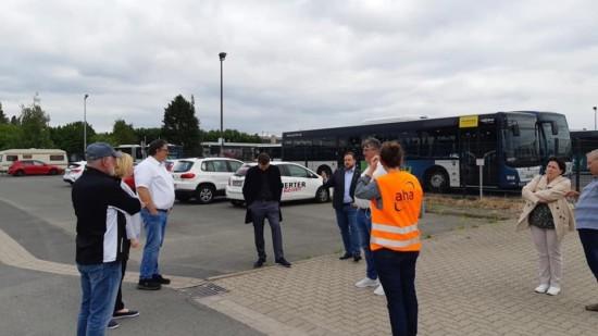 Mehrere Personen stehen auf einem Parkplatz. Im Hintergrund Autos und ein Bus.