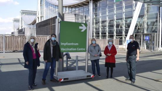 Fünf Personen stehen vor einem Schild, das den Weg zum Impfzentrum weist.